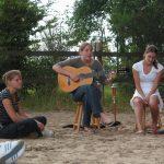 Een vrouw met gitaar zingt voor publiek.