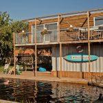 Houten kampeergebouw met natuurlijke zwemvijver