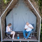 Een wilgenhut met twee mensen ervoor bij Watersportcamping Heeg