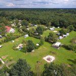 Een luchtfoto van Natuurkampeerterrein De Groene Hen, met veel groen en ruimte.