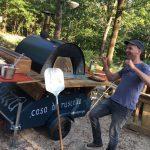 Buiten bij het terras van de Boshut staat een pizza oven op wielen met daarnaast de pizzabakker.
