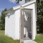 Een inkijkje in een sanitairhuisje, met hierin toilet en douche.