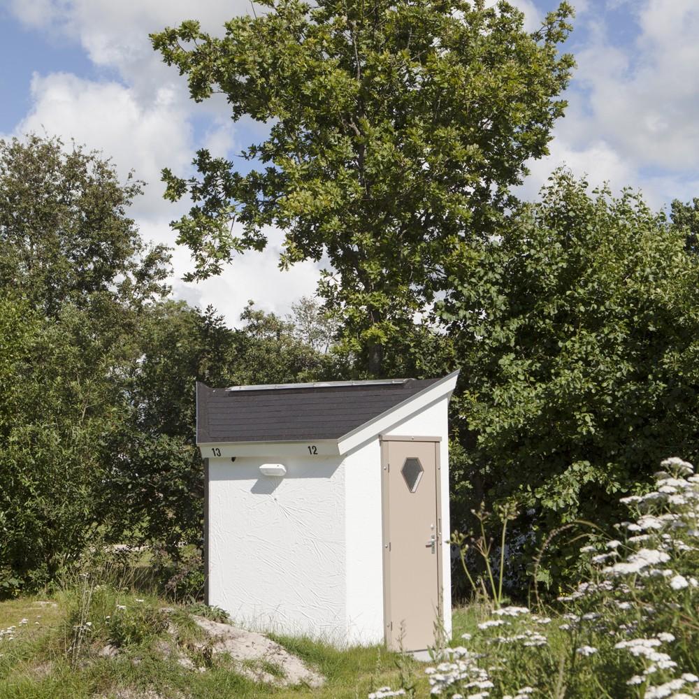 Een wit (privé) sanitair huisje dat hoort bij een kampeerplek.