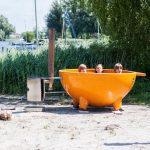 Oranje Dutch tub op een strandje aan een Fries meer bij Watersportcamping Heeg