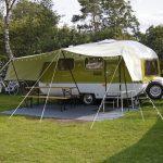Een oude wit-groene caravan met luifel en lampjes
