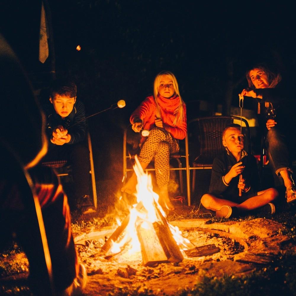 Kinderen rondom een kampvuur in de avond.