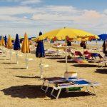 Strandbedjes met gele en blauwe parasols op het strand
