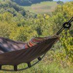 Een bruine hangmat met een gestreept kussen met groene heuvels op de achtergrond