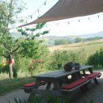 Twee picknicktafels aan elkaar met rode kussens op de banken