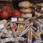Een stapel worsten en hammen op de markt