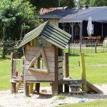 Een houten speelhuisje met op de achtergrond Restaurant de Huiskamer