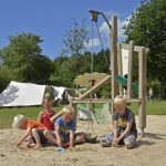 Vier kindjes aan het spelen in de zandbak op het kampeerterrein