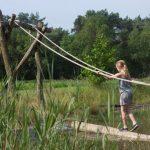 Een meisje op een boomstam die het water overbrugt