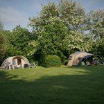 Twee tenten op een ruim opgezet groen kampeerveld