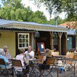 Een terras met 5 mensen aan een tafel, voor Restaurant de Huiskamer