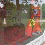Een raamsticker op een vintage camper, met een fotocamera en de tekst Smile