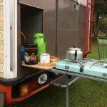 Een oldtimer camper met een keuken die je aan de zijkant naar buiten schuift