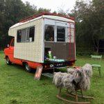 Rode Rik, een vintage camper in rood en wit. Een schommelstoel met schapenvacht