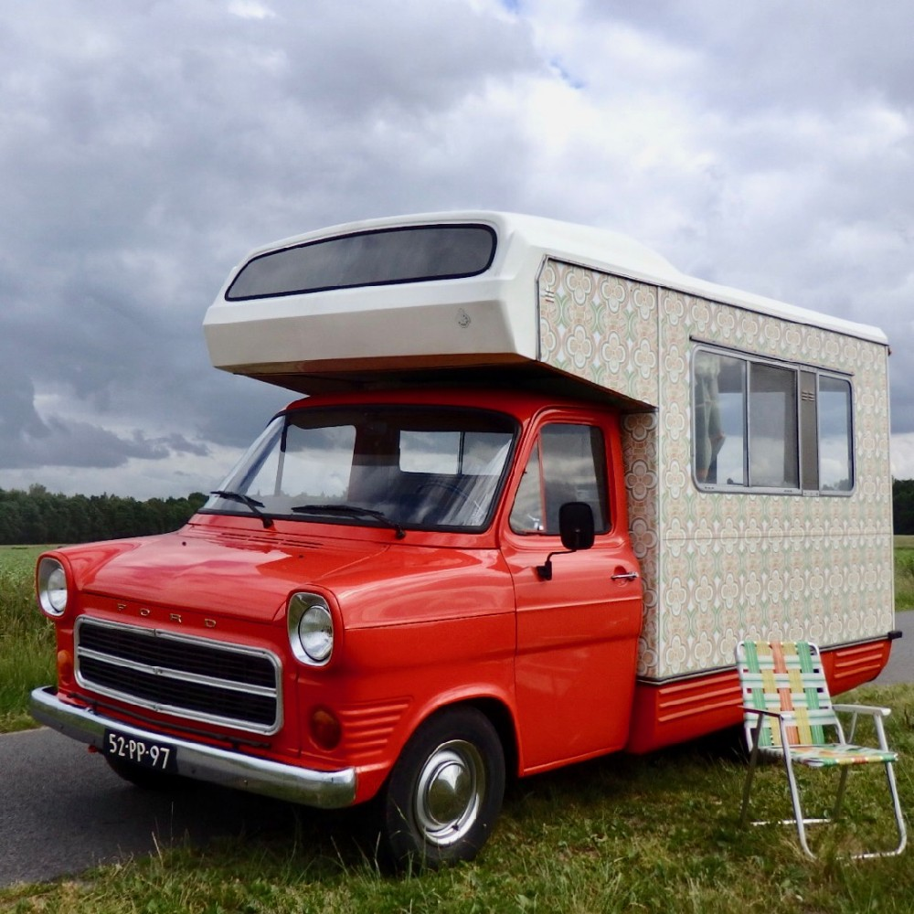Een oude Ford camper, rood met wit