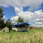 Retro caravan met een blauwe luifel in het gras, met een groen tentje ernaast