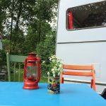 Blauwe tafel, groene en oranje houten stoelen en bloemetje op tafel