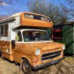 Gele vintage camperbus, een oude Ford