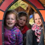 Drie meisjes kijken in de camera, vanuit een speelhuisje