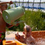 Jongetje in een oranje dutch tub krijgt een gieter water over zich heen