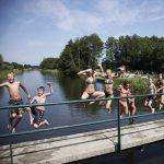 8 kinderen springen van een sluis in het kanaal.