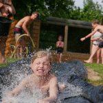 Kinderen aan het buikschuiven op een waterbaan.