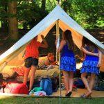 Een open tent met meisjes op de bedden en toeschouwers