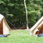 Twee halve tenten met voeten er uit in het bos