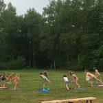 Een groep mensen dat buiten op het gras een les yoga volgt.