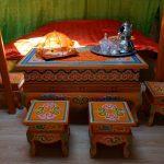 De yurt van binnen met tradionele oranje houten meubels.