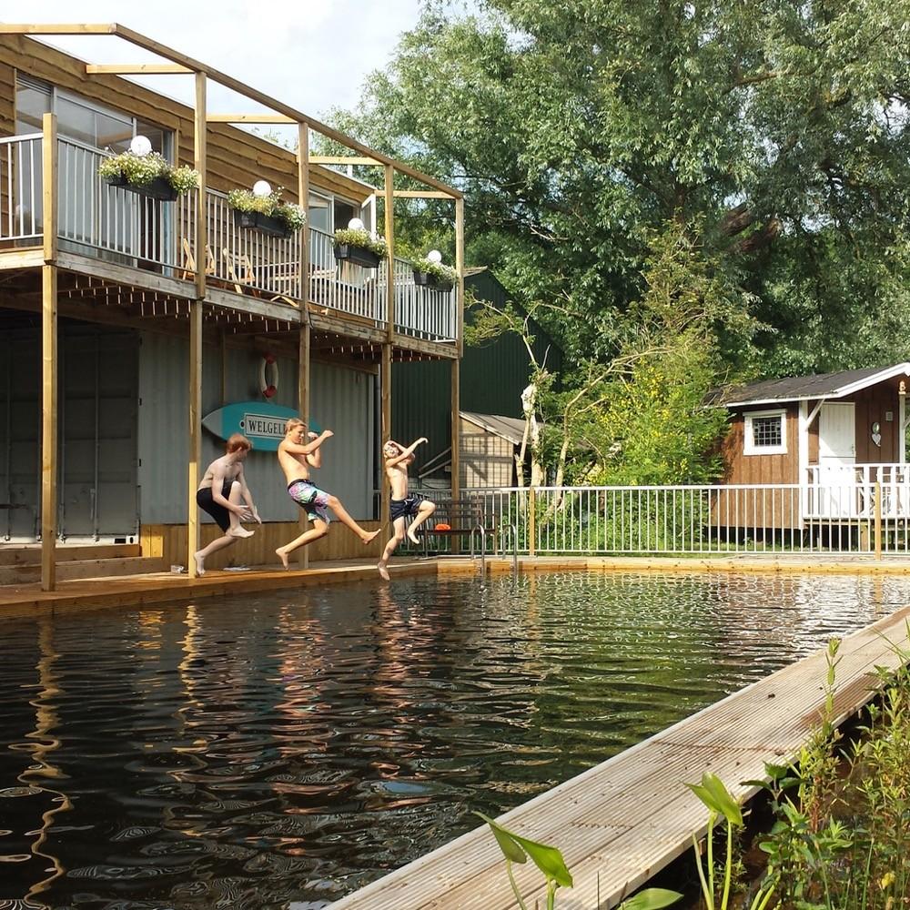 Drie jongens springen in het zwembad op de camping