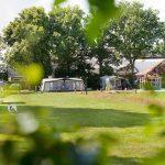 Een open kampeerveldje met tenten, naast de boederij