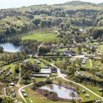 Een luchtfoto van de camping, met bossen, water en caravans