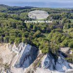 Een luchtfoto van de krijtrotsen met op de achtergrond in de bossen de camping