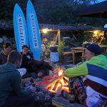 Een brandend vuur met een groep jongeren en twee surfplanken met de naam Welgelegen