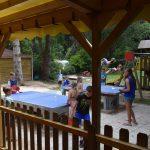 Kinderen aan het pingpongen met blauwe tafels