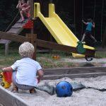 Een jongetje met blonde krullen in een zandbak