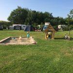 Kampeerveld met caravans, camper, zandbak en spelende kinderen