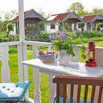 Een veranda met wit tafeltje, zomerse bloemetjes en een rode lantaarn