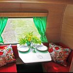 Zithoek in oude caravan met rode kussens en groene gordijntjes