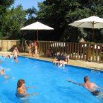 Gasten in een zwembad met houten hekje eromheen