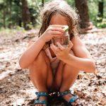 Een kindje zit gehurkt in het glazen potje te kijken waarin ze beestje heeft gevangen