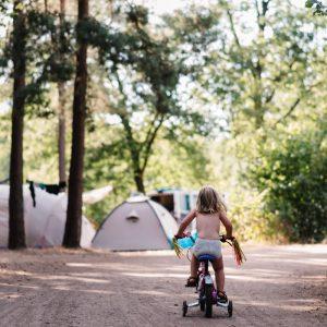 Een peuter op een driewieler van achteren, met op de achtergrond tenten en bomen