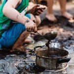 Een kind speelt met pan en soeplepel in de modder