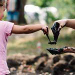 Een kind speelt met moeder en pollepel in de modder