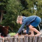 Een kind kruipt op handen en voeten over een balk.
